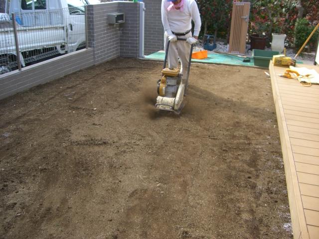 天然芝処理後、転圧プレートで土台を整地作業。