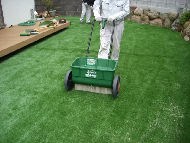 人工芝敷設後、珪砂を専用の砂撒き機で充填します。